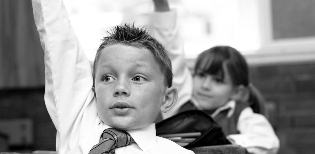 Young Boy at School Raising His Hand to Answer in Class (Image: Royalty-Free/Corbis)